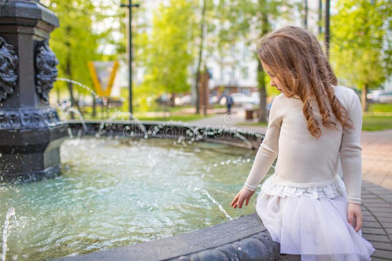 Cute little girl playing by city fountain on hot and sunny summer day. Child having fun with water in summer. Active leisure for k royalty free stock image
