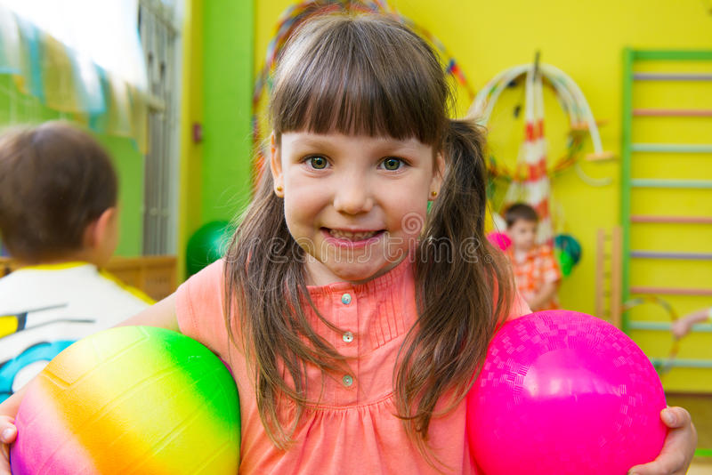 Cute little girl playing at daycare gym stock images