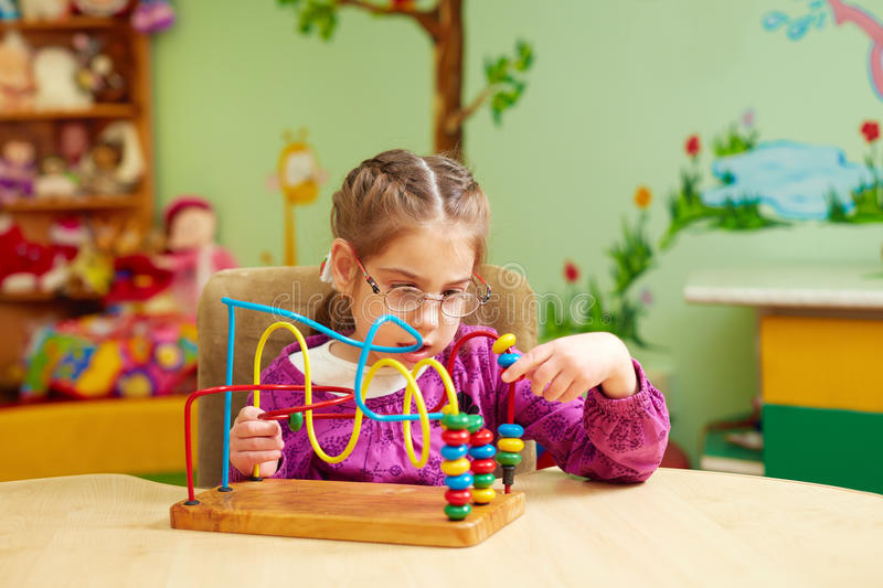 Cute little girl playing with developing toy in kindergarten for kids with special needs royalty free stock photography