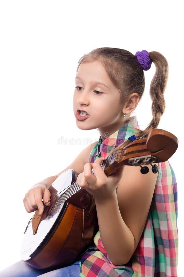 Cute little girl playing on domra. Studio photo stock photo