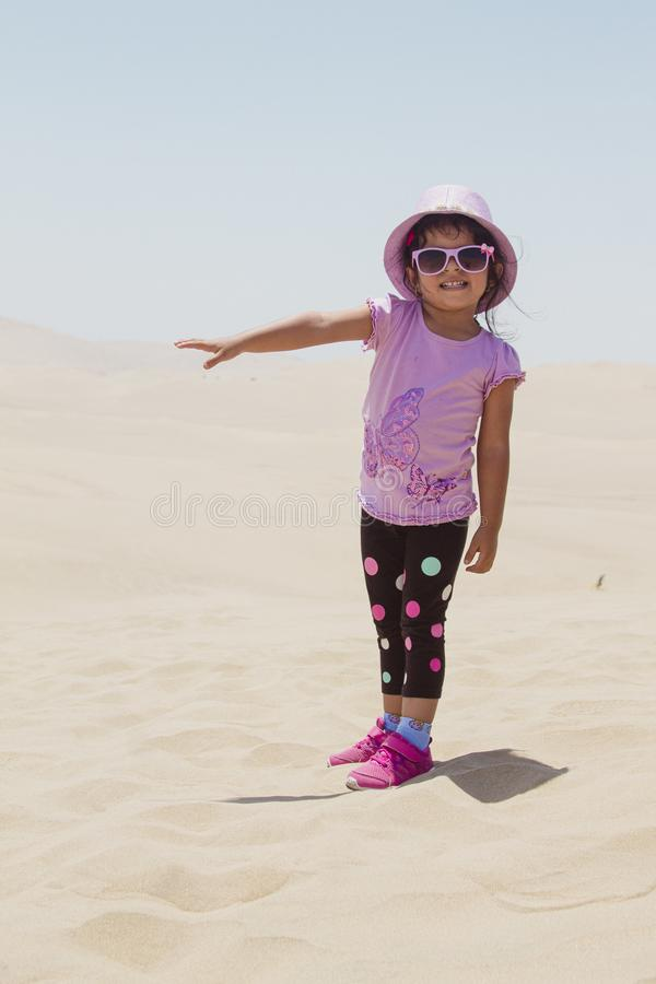 Cute little girl playing in the dunes royalty free stock photo