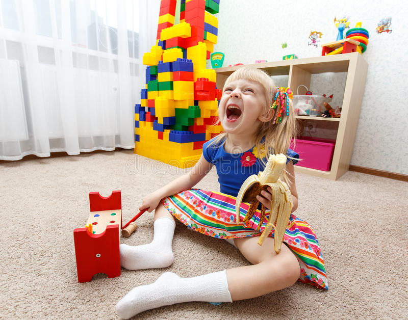 Cute little girl playing and eating banana in daycare royalty free stock photography