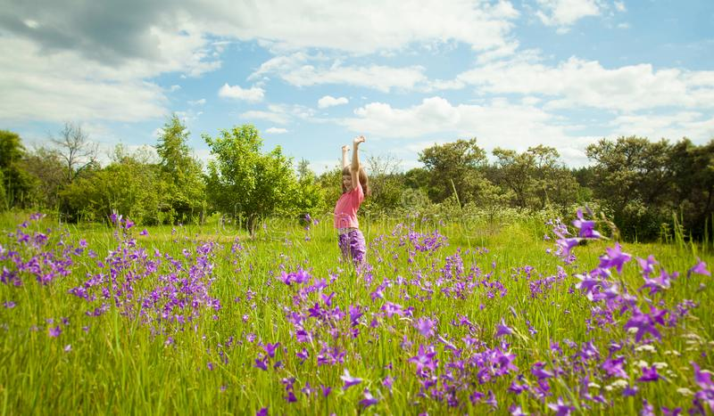 Cute little girl playing in a green summer meadow royalty free stock images