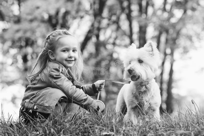 Cute little girl is playing with her dog in autumn park. Happe childhood. Autumn time. Funny baby with dog outdoors. stock photography