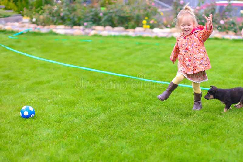 Cute little girl playing with her puppy in the yard. Cute girl playing with her puppy in the yard royalty free stock images