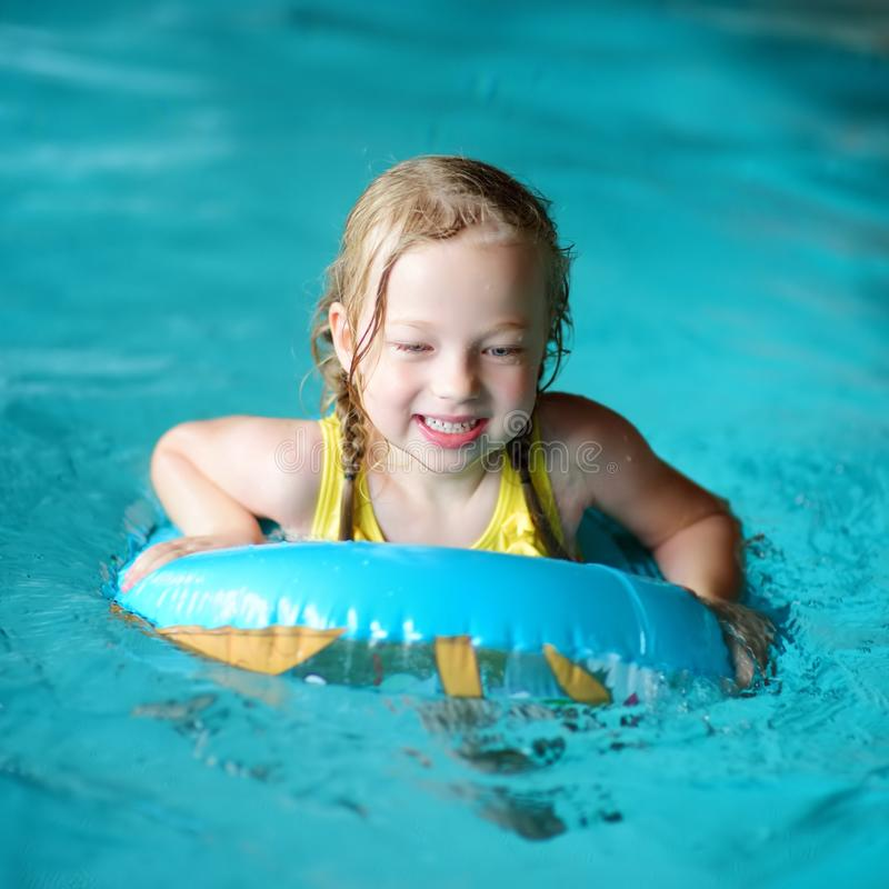 Cute little girl playing with inflatable ring in indoor pool. Child learning to swim. Kid having fun with water toys. Family fun in a pool stock images