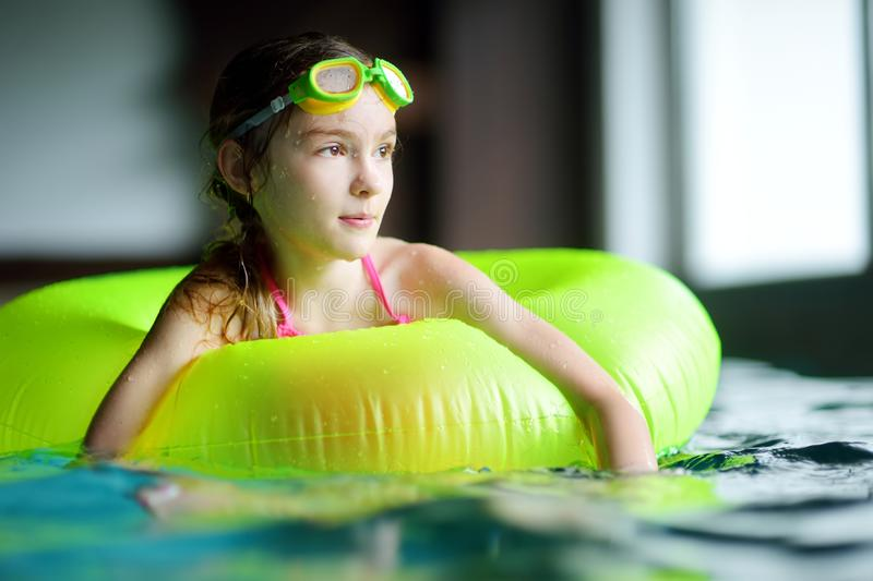 Cute little girl playing with inflatable ring in indoor pool. Child learning to swim. Kid having fun with water toys. Family fun in a pool royalty free stock image