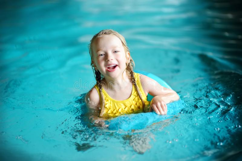 Cute little girl playing with inflatable ring in indoor pool. Child learning to swim. Kid having fun with water toys. Family fun in a pool stock photos