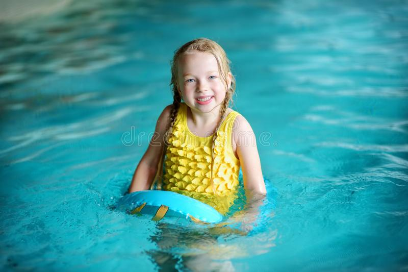 Cute little girl playing with inflatable ring in indoor pool. Child learning to swim. Kid having fun with water toys. Family fun in a pool royalty free stock photo