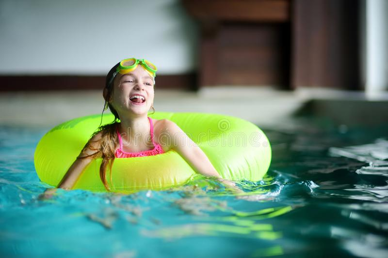 Cute little girl playing with inflatable ring in indoor pool. Child learning to swim. Kid having fun with water toys. Family fun in a pool stock image