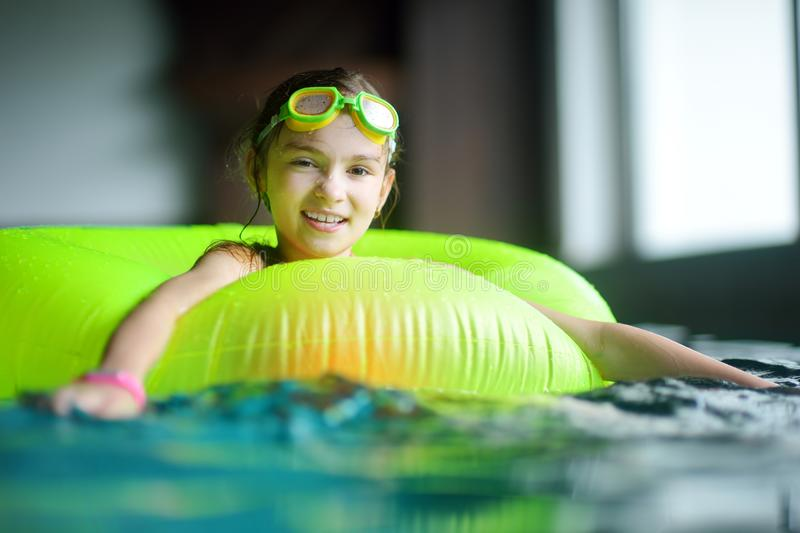 Cute little girl playing with inflatable ring in indoor pool. Child learning to swim. Kid having fun with water toys. Family fun in a pool royalty free stock photography