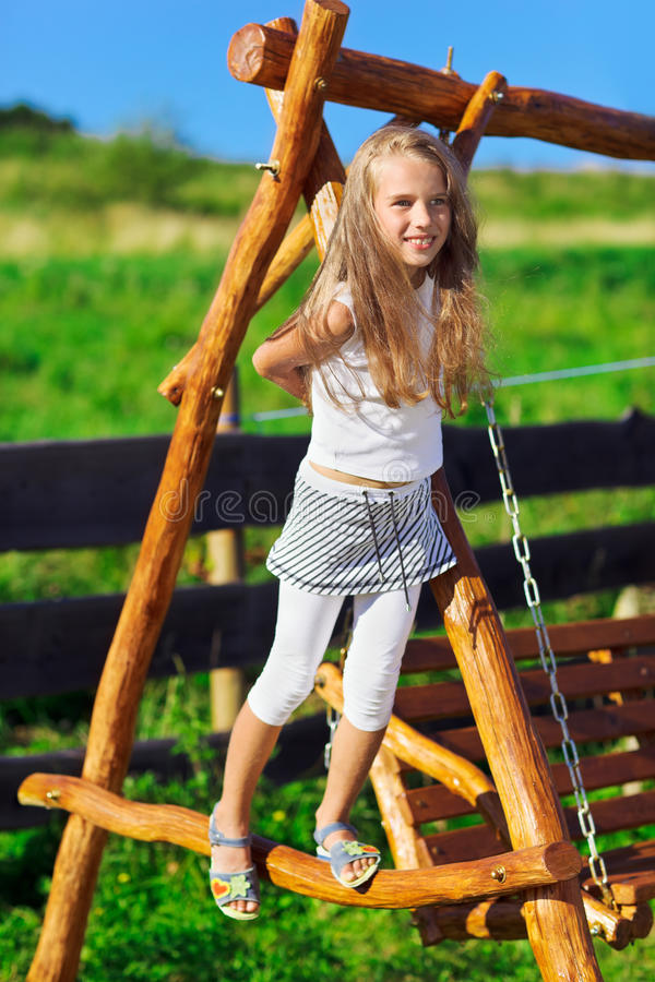 Free Cute Little Girl Playing On Wooden Chain Swing Royalty Free Stock Images - 19094389