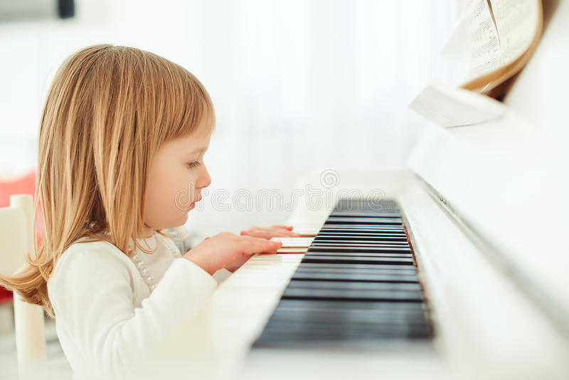 Cute little girl playing piano in light room. royalty free stock images