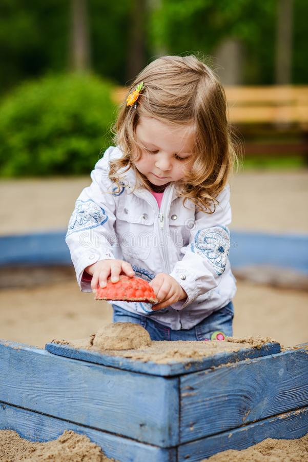 Cute little girl playing with sand at kids playground royalty free stock photos