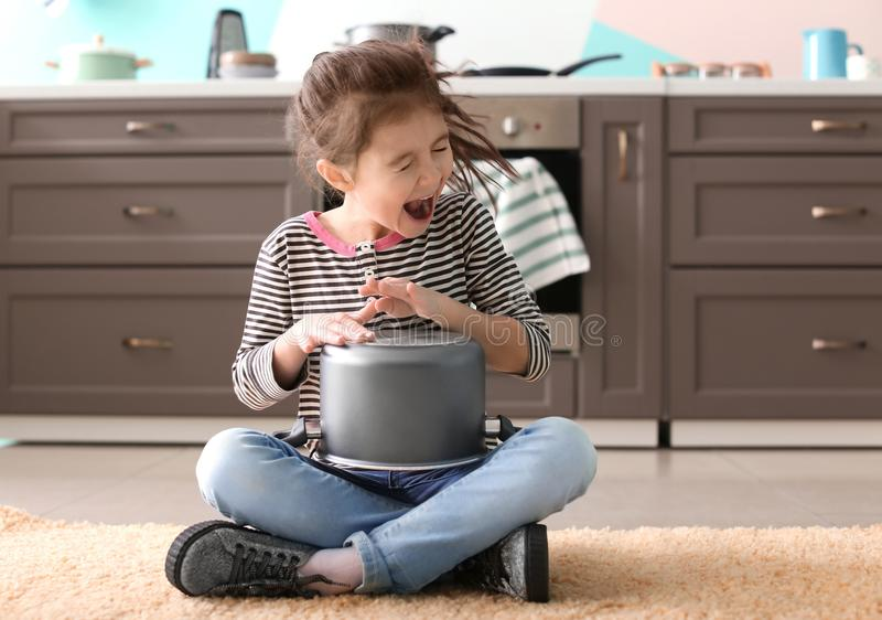 Cute little girl playing with saucepan. As drum indoors royalty free stock photography