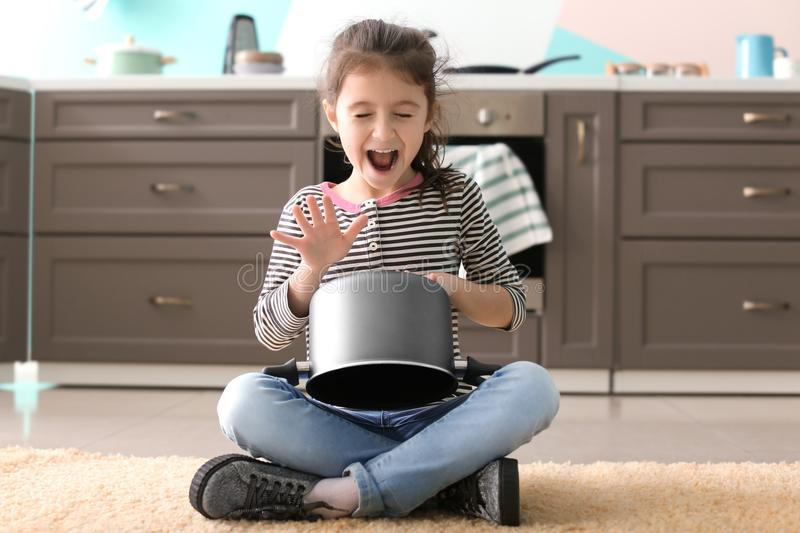 Cute little girl playing with saucepan. As drum indoors stock photos
