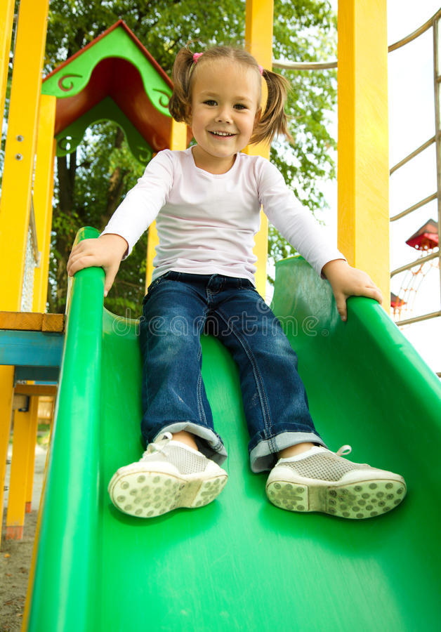 Cute Little Girl Is Playing On Slider Royalty Free Stock Photos