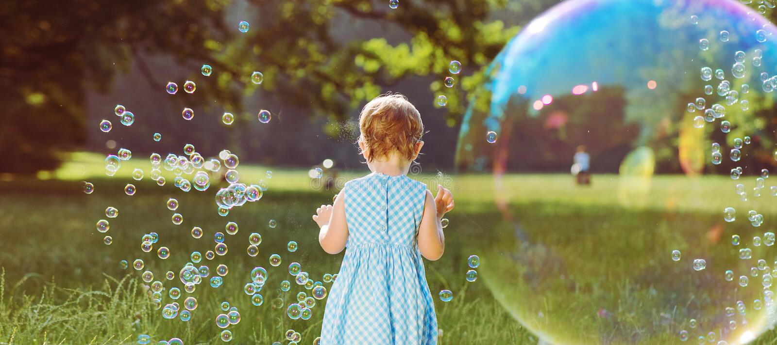 Cute little girl playing the soap bubbles stock image