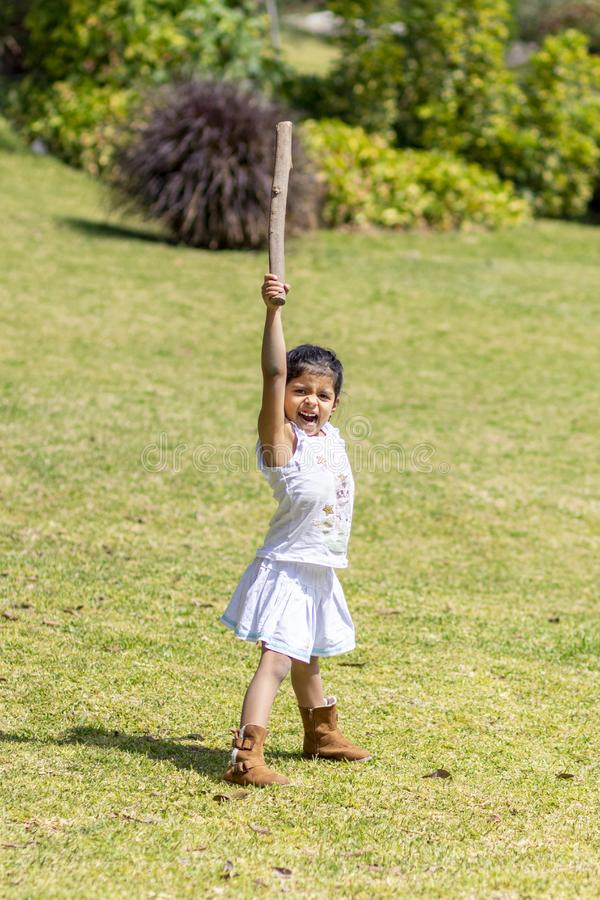 Cute little girl playing with a stick royalty free stock photos
