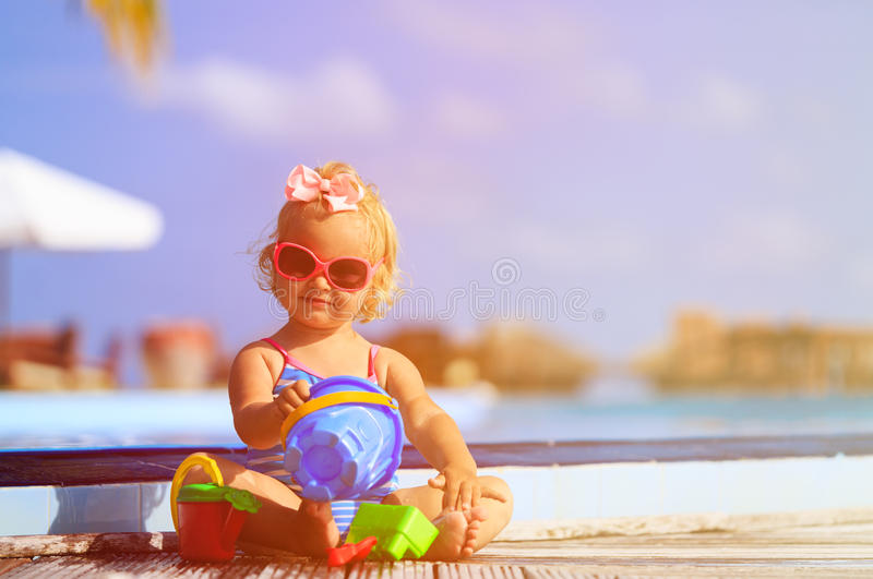 Cute little girl playing in swimming pool at beach. Cute little girl playing in swimming pool at tropical beach royalty free stock images