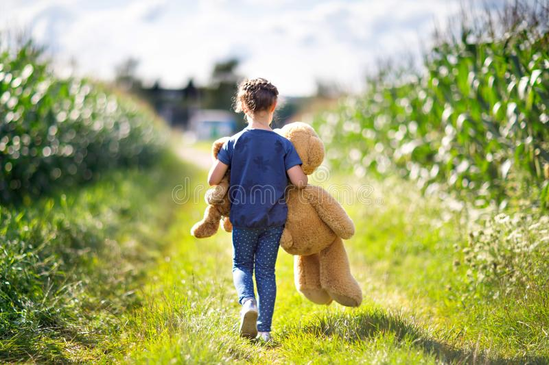 Cute little girl playing with two push toy teddies. Kid holding huge bear and small bear and walking in nature landscape royalty free stock image