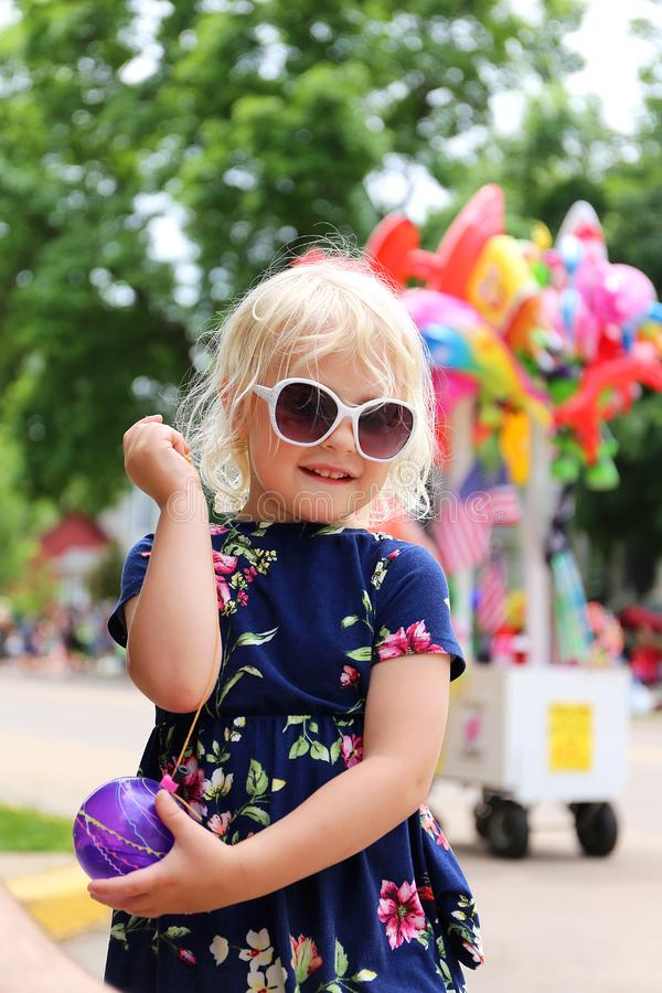 Cute Little Girl Playing with Water Balloon Yoyo at Small Town American Parade. A happy little blond girl child is smiling as she plays with a water balloon yoyo royalty free stock photos