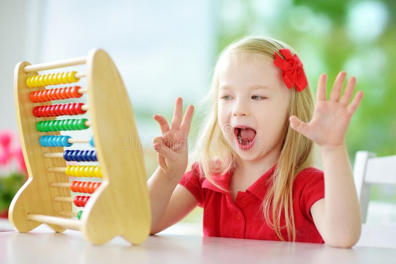 Cute little girl playing with abacus at home. Smart child learning to count. royalty free stock image
