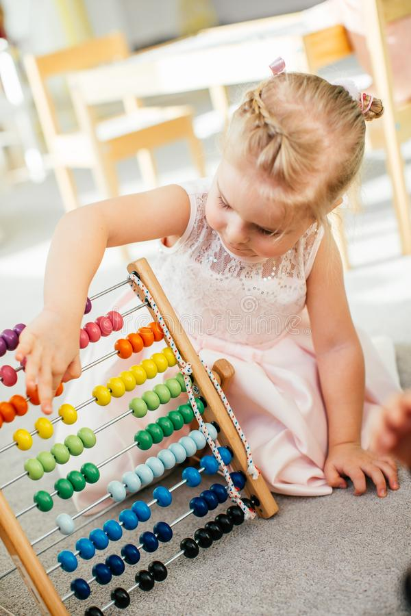 Cute little girl playing with wooden abacus at home. Smart child learning to count. Preschooler having fun with educational toy at stock images