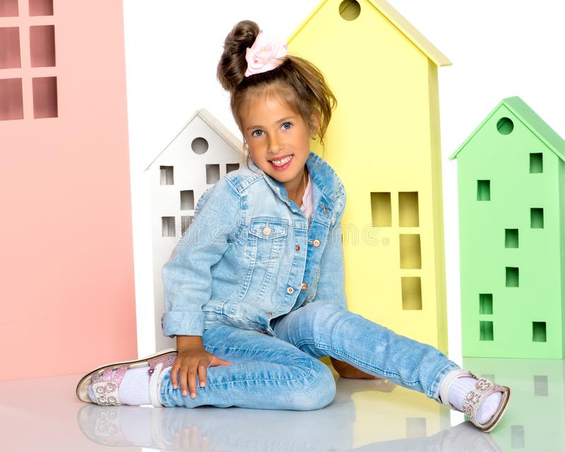 Little girl is playing with wooden houses. royalty free stock photo