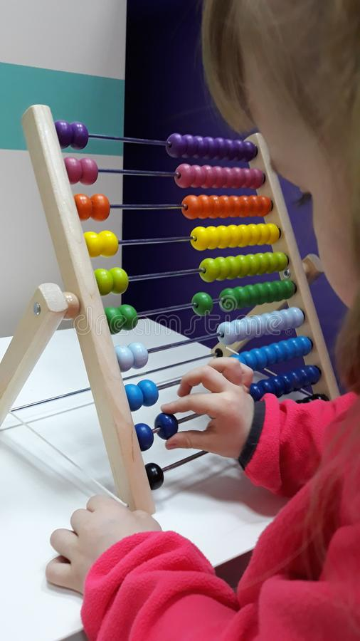 Cute little girl plays wooden abacus. Baby girl counting with help of an abacus. Smart child learning to count. stock images