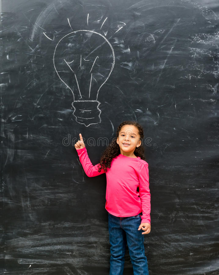 Cute little girl pointing on a drawn lamp royalty free stock image
