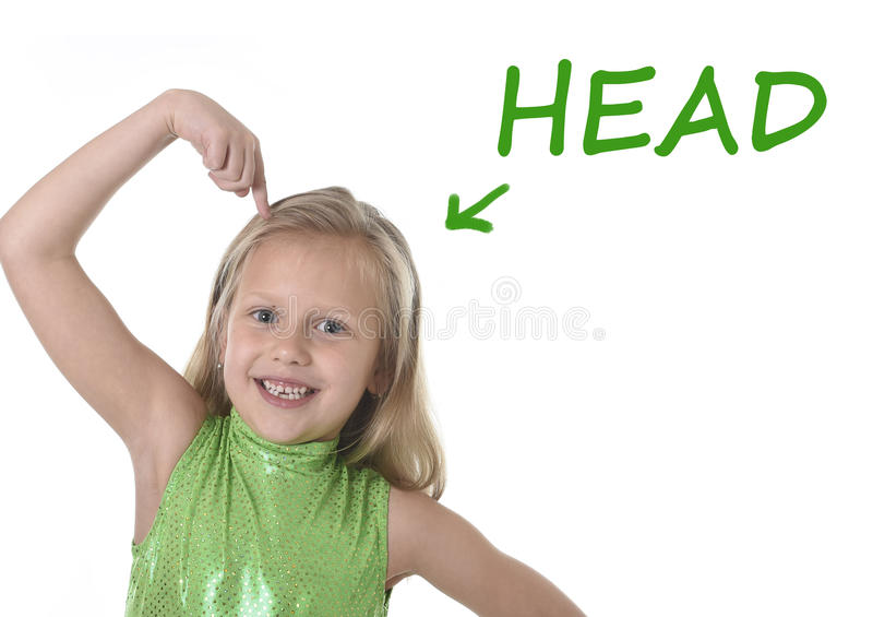 Cute little girl pointing her head in body parts learning English words at school royalty free stock photography