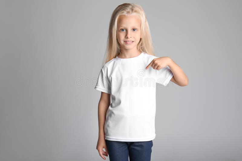 Cute little girl pointing at her t-shirt on grey background stock photo
