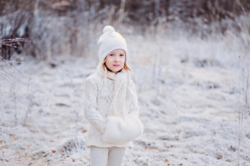 Cute little girl portrait on the walk in winter snowy frozen forest royalty free stock images