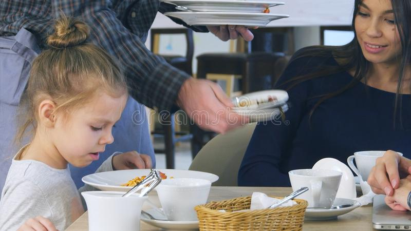 Cute little girl pouring cheese in her spaghetti in italian restaurant while her young parents have ate their vegetable. Salads yet. Professional shot on Lumix stock image