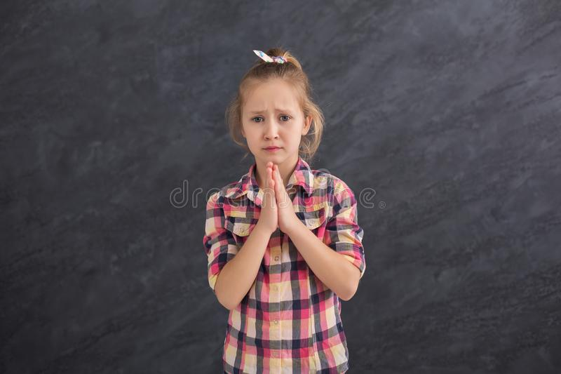Cute little girl begging something on grey background. Cute little girl praying, begging something, looking on camera on grey background royalty free stock photos