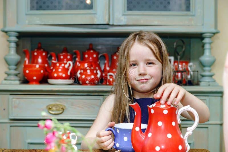 Cute little girl preparing tea in teapot stock images