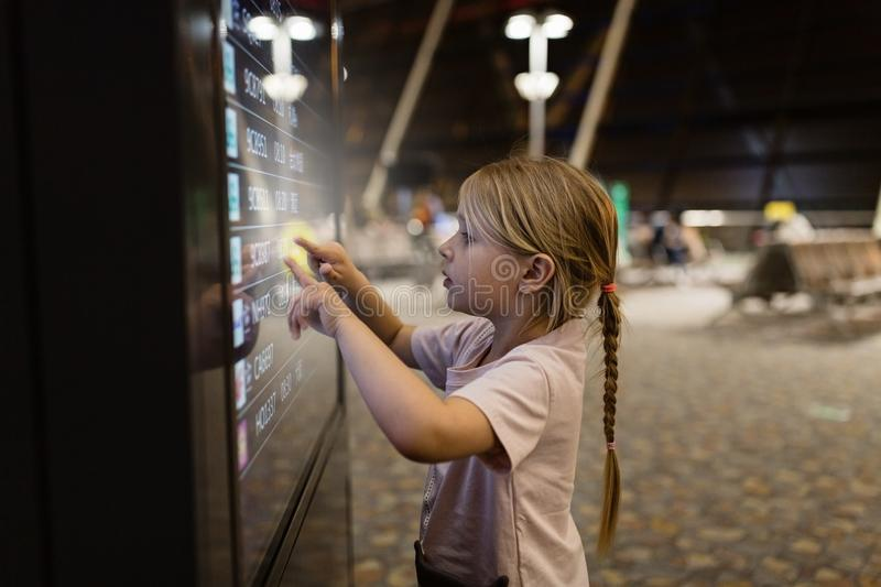 Cute little girl pressing icon on digital touch screen in airport terminal. Kid using technology royalty free stock photos