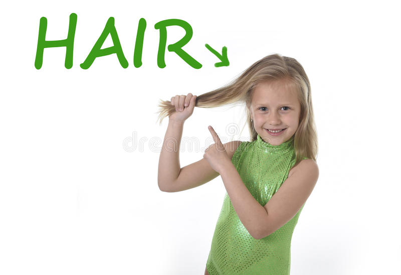 Cute little girl pulling blonde hair in body parts learning English words at school royalty free stock photo
