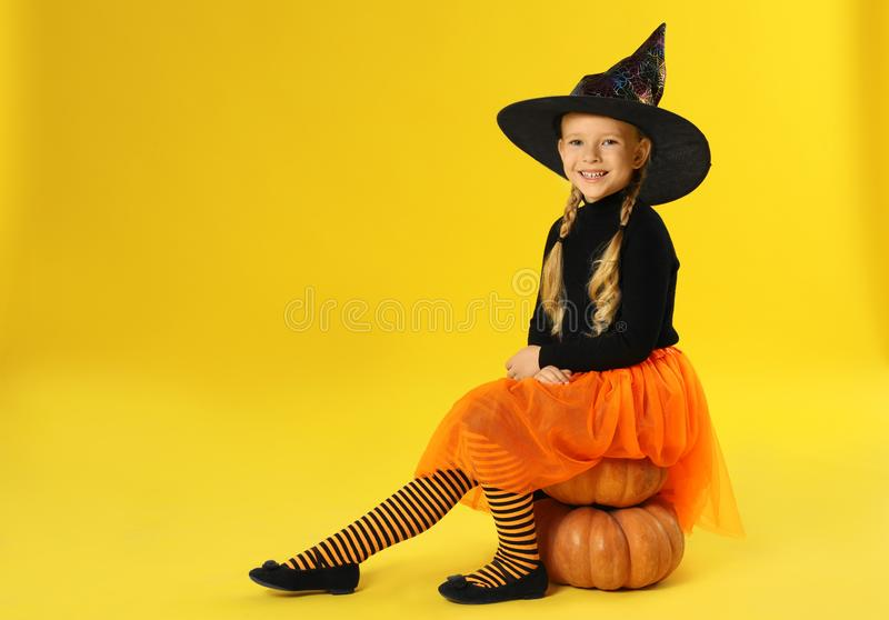 Cute little girl with pumpkins wearing Halloween costume on yellow background royalty free stock photography