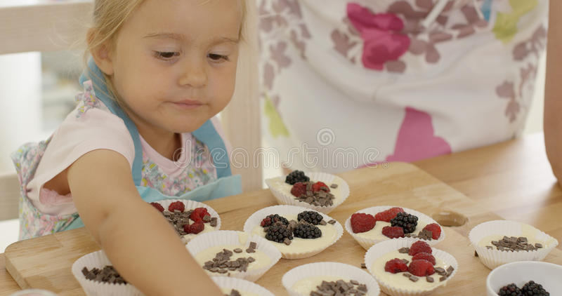Cute little girl putting berries on muffins stock photo