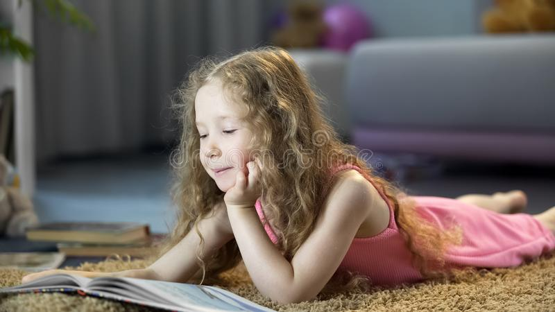 Cute little girl reading adventurous book, lying on floor, spending leisure time royalty free stock photography
