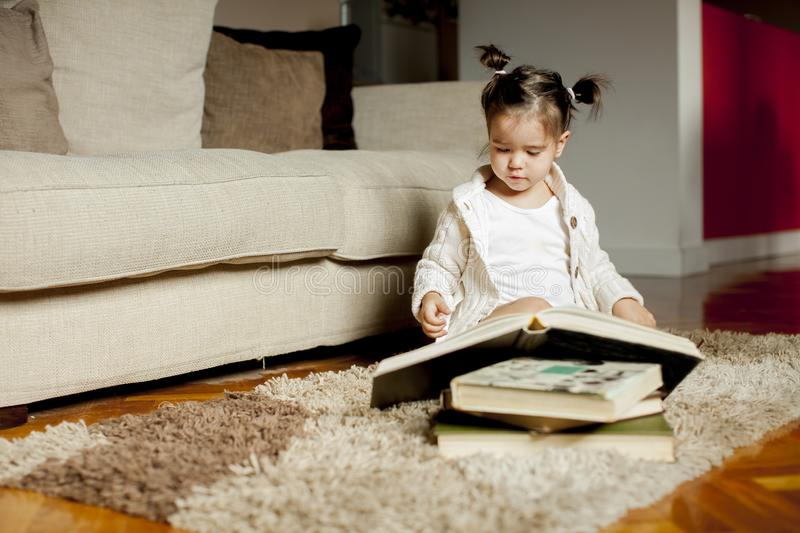 Little girl reading book on the floor in the room stock photo