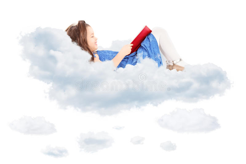 Cute little girl reading a book and laying on cloud royalty free stock photo