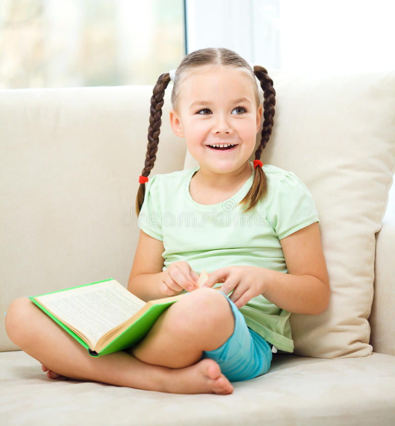 Little girl reads a book stock images