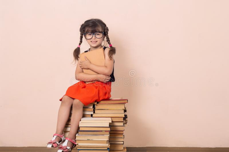 Cute little girl reading book sitting on pile of books. stock photography