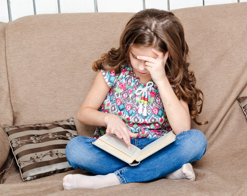 Cute little girl is reading the book on the sofa royalty free stock photos