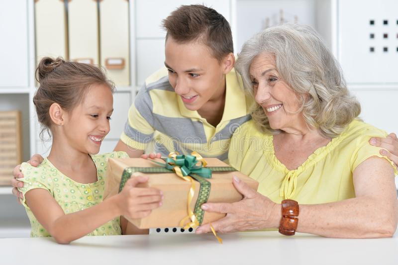 Cute little girl receiving present from grandmother and brother stock image