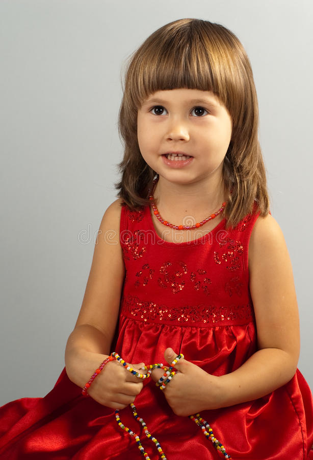 Download Cute Little Girl In A Red Dress With Necklace In H Stock Photo - Image: 12056694