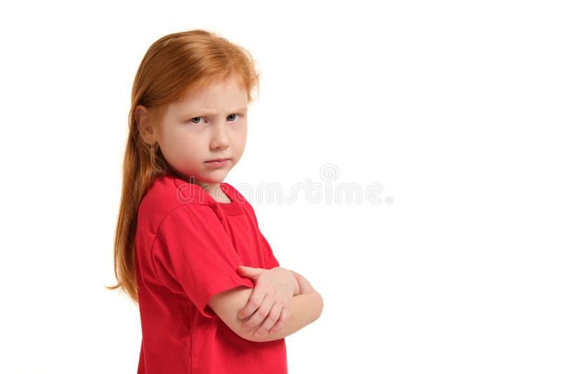 Cute little girl with red hair and folded arms looking angry isolated white background. Cute little girl with red hair and folded arms looking angry and upset in royalty free stock photography